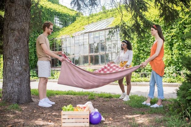 Picknick gebied. lange lachende man en twee langharige meisjes staan te denken met deken in handen in het park op zonnige dag