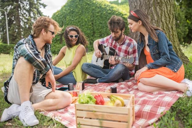 Picknick, gitaar. betrokken jonge bebaarde man die gitaar speelt en geïnteresseerde vrienden luistert die picknicken op een mooie middag