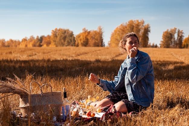 Picknick in de frisse lucht: een jonge vrouw in een spijkerjasje en een jurk die een appel eet en geniet van de natuur, zittend op een plaid met een picknickmand, appels, wijn.