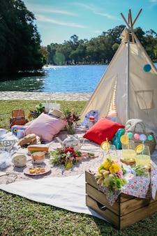 Picknick in deken en tent in het park. eten, bekers, kussens en bloemen.