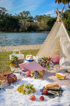 Picknick in deken en tent in het park met het meer.