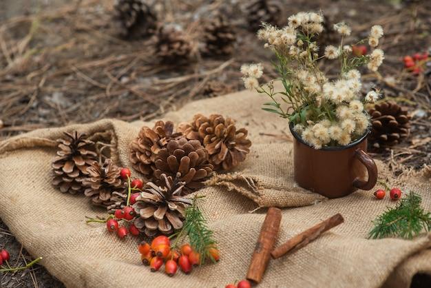 Picknick in een dennenbos. een metalen vintage cirkel met bosbloemen, sparren takken, kaneelstokjes en kegels op een dorpstafelkleed. nieuwjaar en kerstmis achtergrond, briefkaart