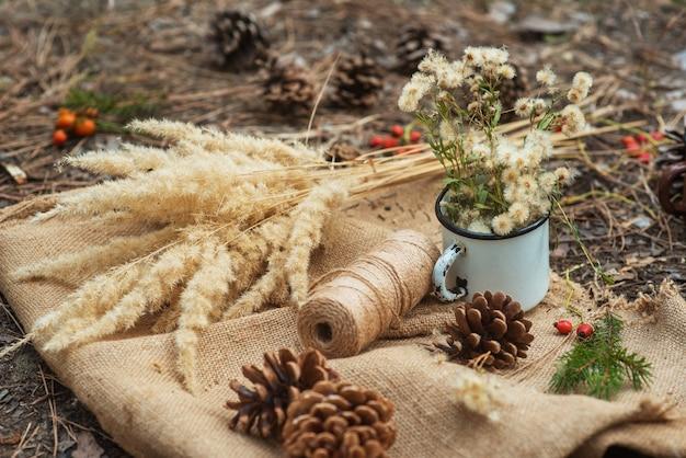 Picknick in een dennenbos. een metalen vintage mok met bosbloemen, sparren takken, kaneelstokjes, kronkeldraden en kegels op het dorpstafelkleed. nieuwjaar en kerstmis achtergrond, briefkaart