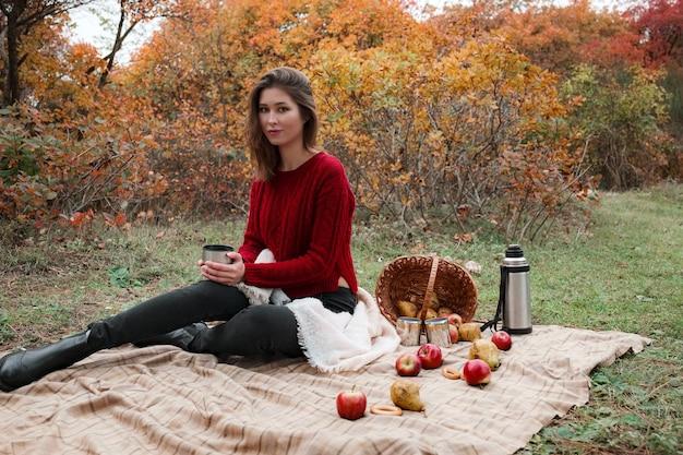 Picknick in het herfstbos. een mooie aziatische vrouw in een rode trui zit op een plaid bij een mand met thermoskan, appels en peren
