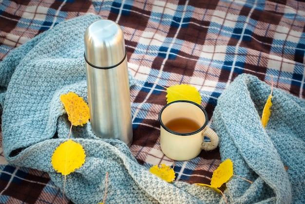 Picknick in het herfstbos. op een geruite retro thermoskan, mok en sjaal. oranje bladeren. de herfst is gekomen.