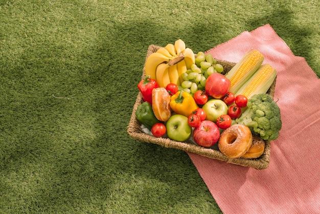 Picknick in het park op het gras: tafelkleed, mand, gezonde voeding en accessoires, bovenaanzicht