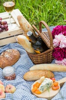 Picknick in het park op het gras: wijn, kaas en brood