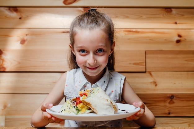 Picknick. klein meisje met vegetarische wrap ijsberg