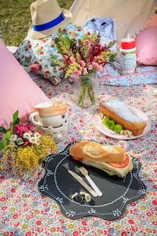Picknick lunch in het park. broodjes, appels en bloemen.
