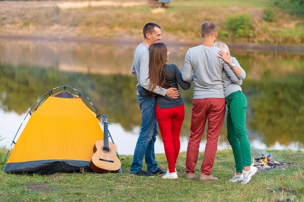 Picknick met vrienden binnen bij meer dichtbij het kamperen tent. bedrijfsvrienden die wandelpicknick hebben