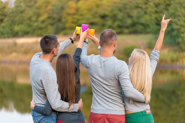 Picknick met vrienden binnen bij meer dichtbij het kamperen tent. bedrijfsvrienden met wandelpicknick natuur. wandelaars ontspannen tijdens het drinken. zomerpicknick. leuke tijd met vrienden.