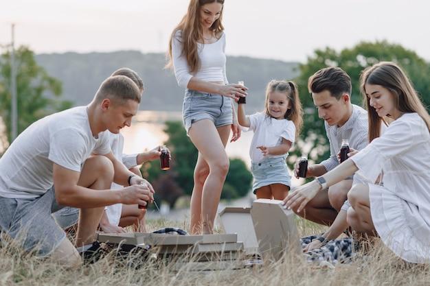 Picknick met vrienden die pizza eten en dranken drinken