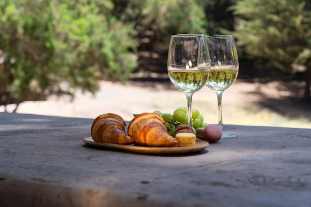 Picknick met witte wijn en croissants in het bos