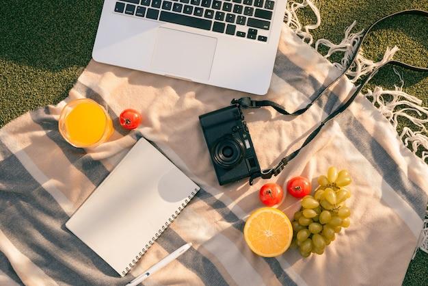 Picknick op een buitentafel met vers fruit, laptop, telefoon, camera