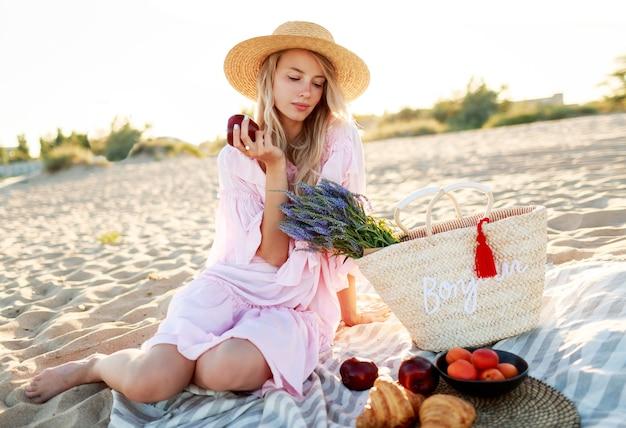 Picknick op het platteland in de buurt van de oceaan. sierlijke jonge vrouw met blonde golvende haren in elegante roze jurk genieten van vakantie en eten van fruit.