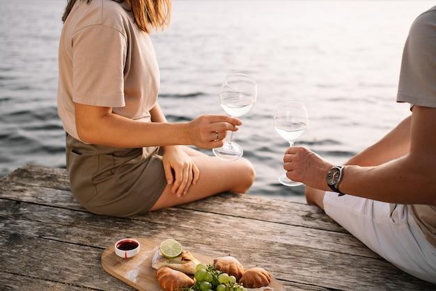 Picknick van een jong stel op de pier bij het meer, glazen wijn