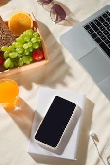 Picknickconcept en zomervakantie met laptop, telefoon, sap, fruit, oortelefoon op lichte achtergrond.
