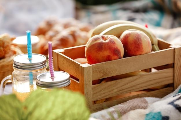 Picknicken in het park. close up van vers fruit, ijskoude mousserende dranken op een warme zomerdag. picnic lunch. selectieve aandacht