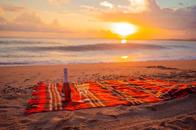 Picknicken op het strand bij zonsondergang