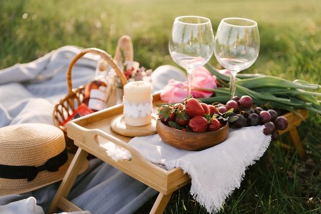 Picknickmand met aardbeien, druiven en broodjes op het groene gras in de tuin