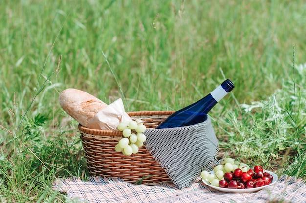 Picknickmand met drankjes en eten op doek in tuin