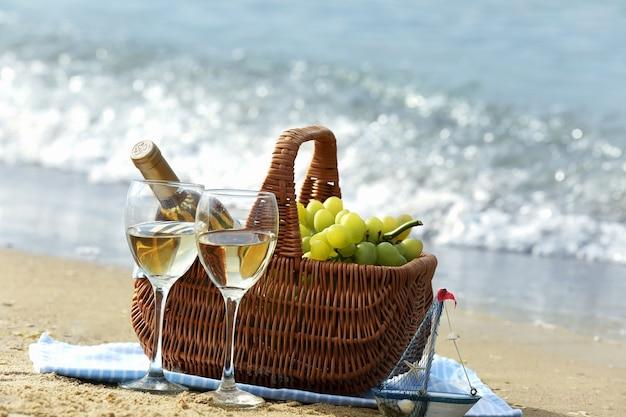 Picknickmand met fles wijn op zandstrand