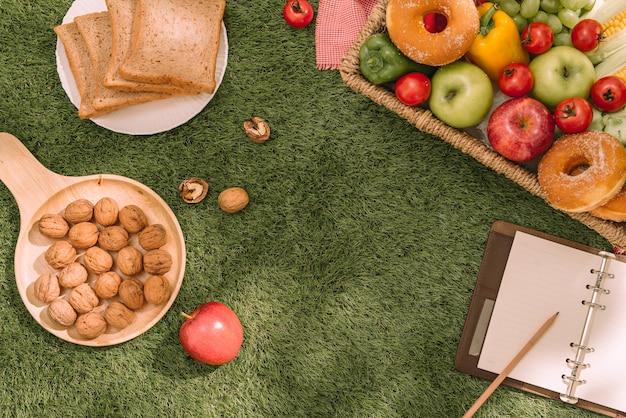 Picknickmand met fruit en boek op de grasachtergrond
