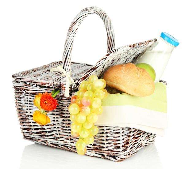 Picknickmand met fruit en een fles melk, op wit