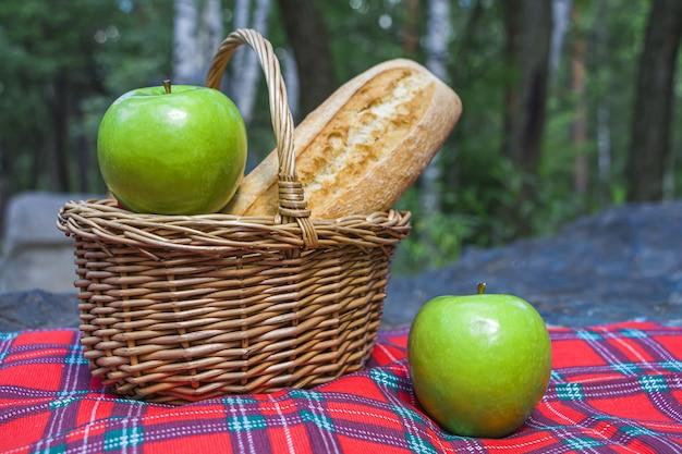 Picknickmand met stokbrood en fruit op geruite doek op rotsen.