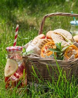 Picknickmand met voedsel op groen zonnig gazon
