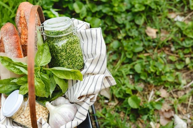 Picknickmand voor het bereiden van vers lookbrood of bruschetta, stokbrood voorgerecht met traditionele italiaanse saus - zelfgemaakte pesto in een glazen pot met ingrediënten basilicum, pijnboompitten en brood buitenshuis.