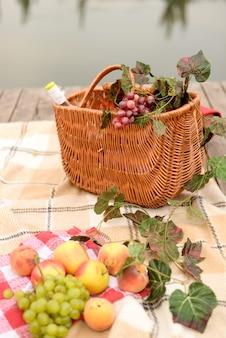Picknickmand, wijn en fruit met uitzicht op het meer