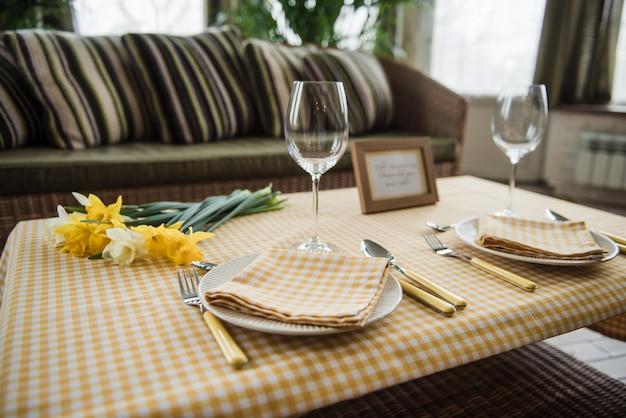 Picknickset. bestek, tafelkleed, mand, lepels, vorken, messen, glazen, servetten. romantische date. familie weekend. gele cel. perfecte familie. narcissuses. een frame voor tekst of foto.