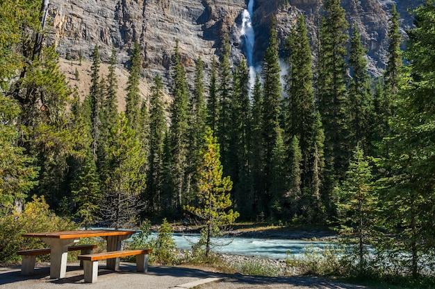 Picknicktafel bij de rivier en de waterval in de zomer met lommerrijk bos eromheen
