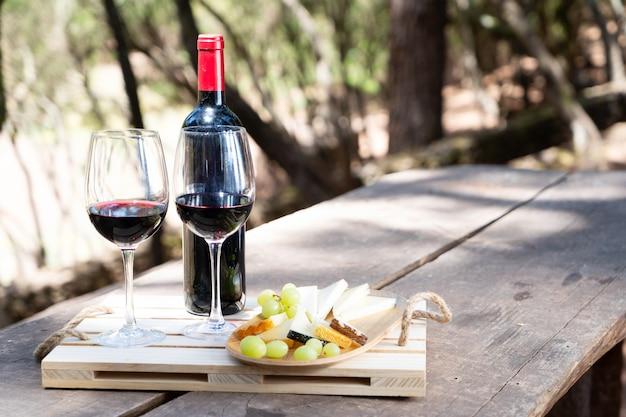 Picknicktafel met rode wijn, brood en kaas met schaduwen overlay