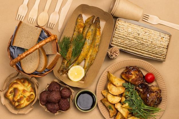 Picknickvoedsel in milieuvriendelijke kartonnen wegwerpschaaltjes. brood mand. bruine achtergrond. plat leggen