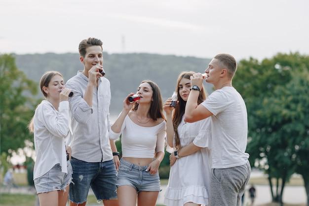 Picknickvrienden met pizza en drankjes drinken en eten met gejuich, zonnige dag, zonsondergang, gezelschap, plezier, koppels en moeder met baby
