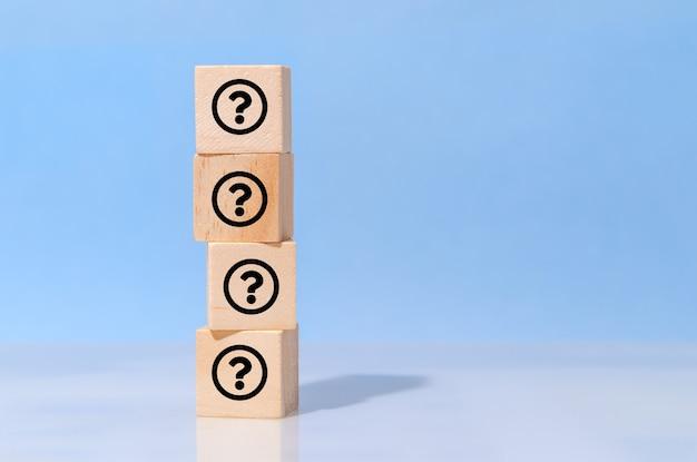 Pictogram vraagteken op houten kubusblok op blauwe achtergrond. faq, antwoord, informatie, communicatie en brainstormconcepten
