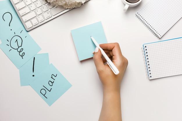 Pictogrammarkeringen op kleverige nota's op bureau op witte hoogste mening als achtergrond.