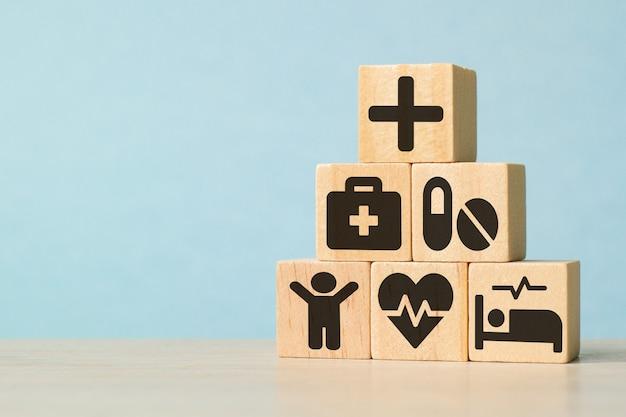 Pictogrammen op houten stuk speelgoed blokken gestapeld in piramidevorm. begint een lichamelijk onderzoek voor gezondheidszorg en ziektekostenverzekering. het concept van verzekering