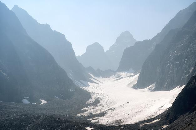 Piek van hoge bergen op koude winterdag vóór nacht.