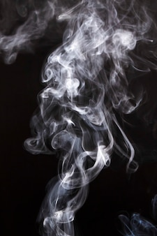 Piekerige rookwolken die op zwarte achtergrond worden uitgespreid