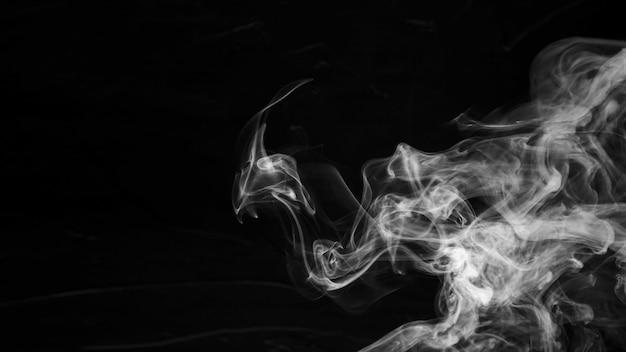 Piekerige witte rook die op zwarte achtergrond wordt uitgespreid
