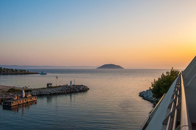 Pier bij zonsondergang, water op de zee vanaf een heuvel, de boot vaart op de zee