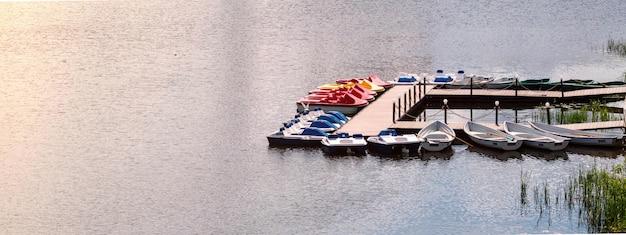 Pier met boten en catamarans voor een wandeling langs de rivier.
