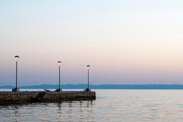 Pier met geparkeerde fiets bij zonsondergang aan de egeïsche zeekust met landlantaarnpalen in griekenland