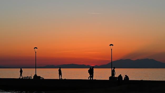 Pier met meerdere vissen en wandelende mensen bij zonsondergang, geparkeerde fiets, landlantaarnpalen, griekenland
