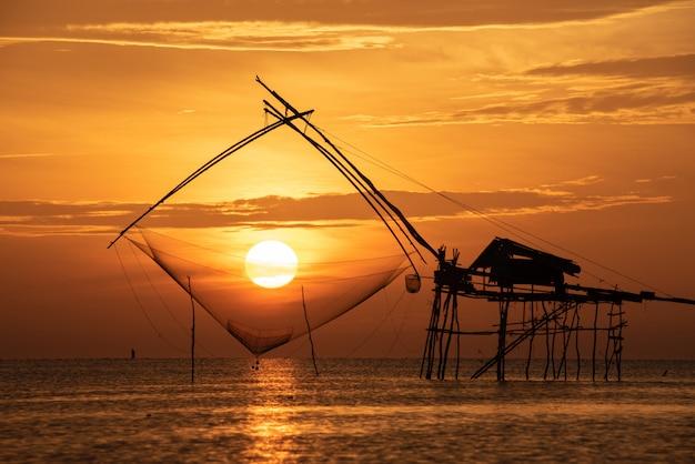 Pier met netten silhouet bij zonsopgang