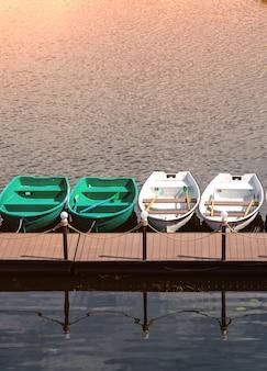 Pier met roeiboten voor romantische rivierwandeling of vissen.