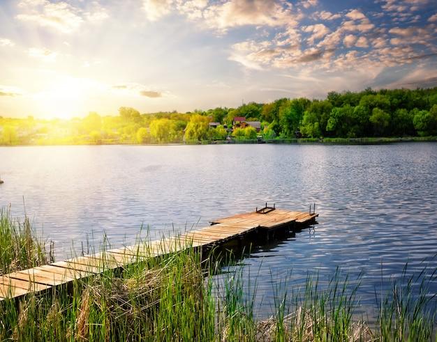 Pier om te vissen op het meer onder de ondergaande zon